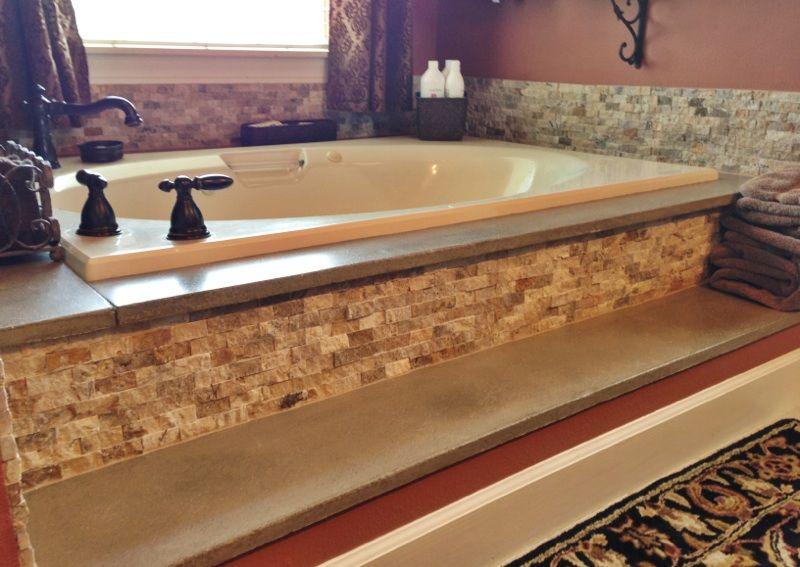 Concrete bathtub surround and travertine stacked stone for How to install granite backsplash in bathroom