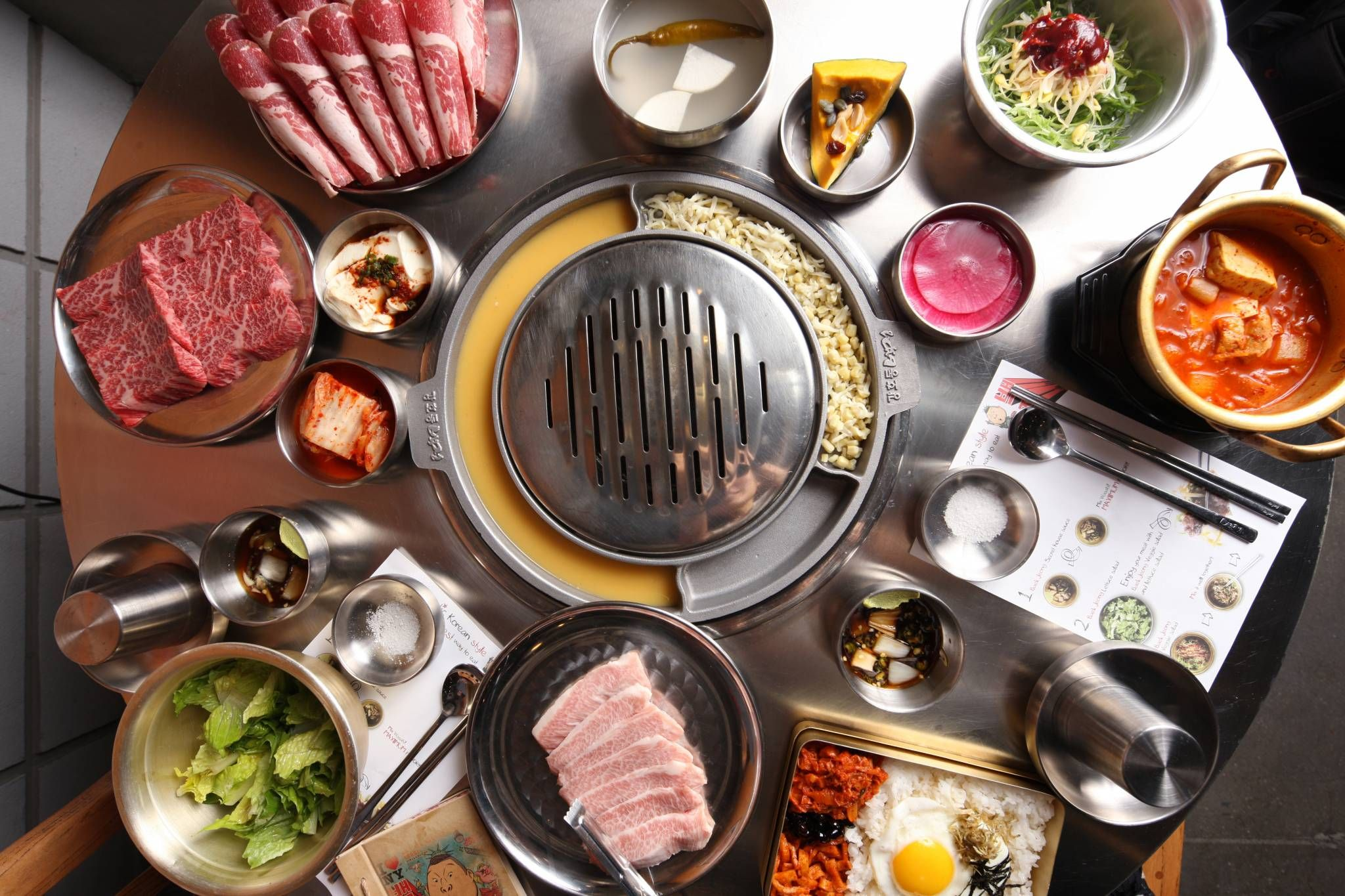 Traditional Korean Bbq Table In Addition To Various Garnishes The Ingredients Include Thinly Sliced Brisket Food Healthy Food Delivery Korean Bbq Restaurant