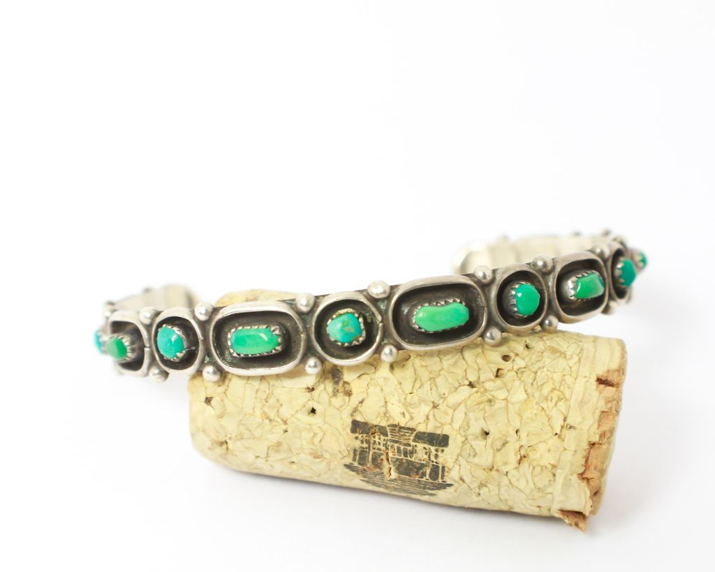 This gorgeous Navajo piece is made with bright green turquoise and sterling silver. The cabochons look beautiful in the bracelet. It's been rescued and restored to beautiful condition.