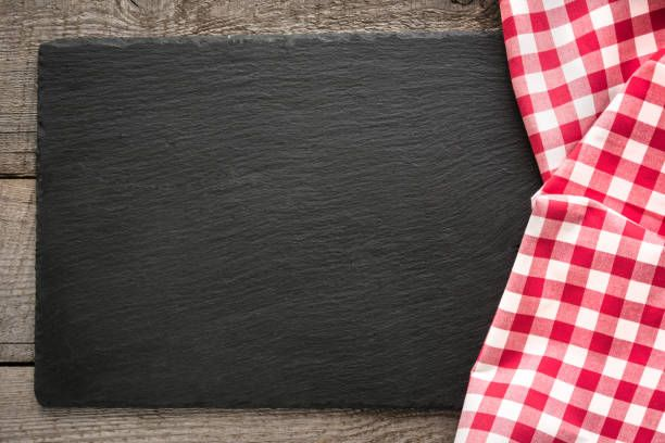 rustic wooden boards red checkered napkin and black slate dish with