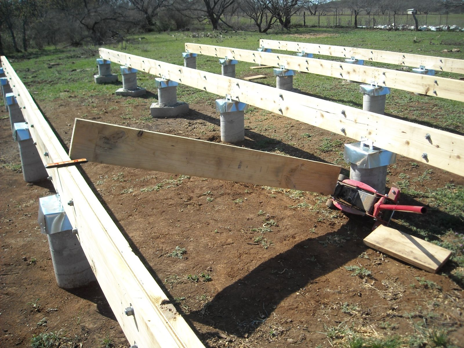 Using floor jack to upright the torqued foundation beams for How to build a pier foundation