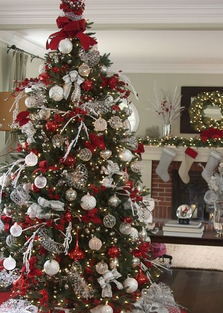 tree toppers are a must for an elegant display silver stretch net ribbon and loops of red velvet glitter ribbon add the finishing touch to this gorgeous