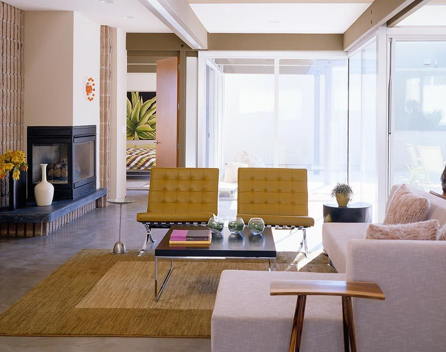 Beige-on-beige tone can have high impact if the contrast is great. The camel-colored area rug provides the perfect foundation for a pair of Mies van der Rohe Barcelona chairs in the same color. By Kenneth Brown Design.