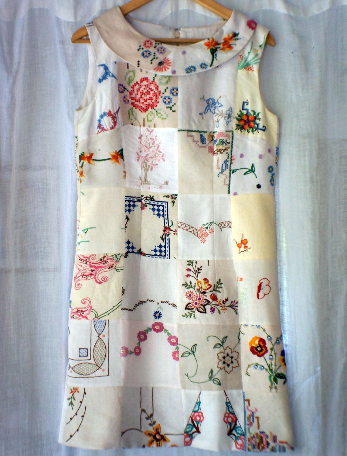 This one of a kind dress will turn heads whenever you wear it! It is made from a lovely selection of repurposed vintage embroidered linen and cotton floral doilleys and is fully lined in a light indian cotton. Closure is with an invisible zip and hook and eye. The dress would fit a large 10 or small 12 and sits just above the knee with a back slit. The wide neck is enhanced with a pieced collar that sits well and gives the dress some definition. I am more than happy to send more detailed…