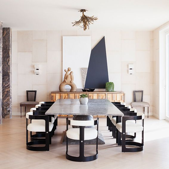 Rectangular marble dining table for 10, with black frame and white upholstered modern chairs, a Malibu Beach House Modern dining set by Kelly Wearstler.