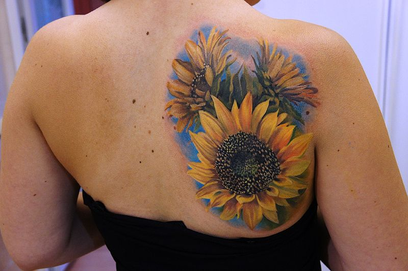 A Sunflower Tattoo On Your Back Is Symbolic Of Femininity And Grace