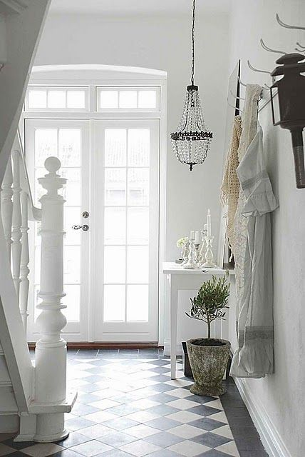 Light and bright white hallway with black and white floor tiles and a low hanging chandelier