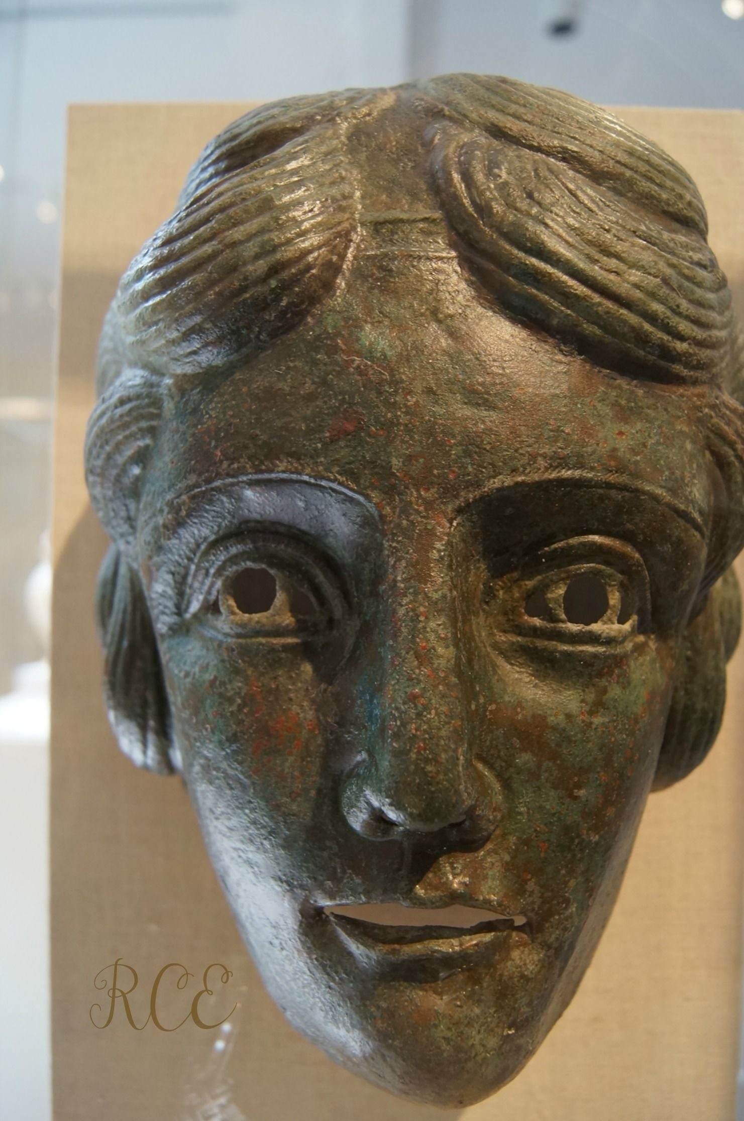 Cavalry sports mask in Bronze. Roman, Mid-imperial, 2nd Century AD. This represents a woman (Amazons -- famous female warriors of the ancient world??) with long, flowing locks of hair tied with a diadem.