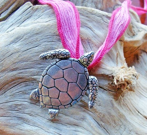 "This beach-inspired pewter sea turtle pendant hangs from a hand-dyed silk ribbon. Choose from 4 ribbon colors. Pendant measures 3/4 X 1 3/4 inches. Ribbon is 36""."