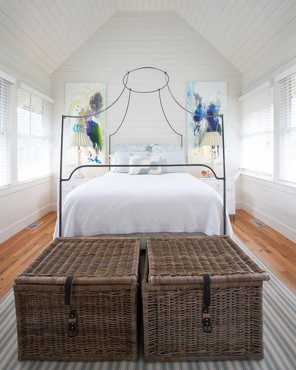 Lovely cottage bedroom features shiplap walls and ceiling over an Italian  Campaign Canopy Bed dressed in