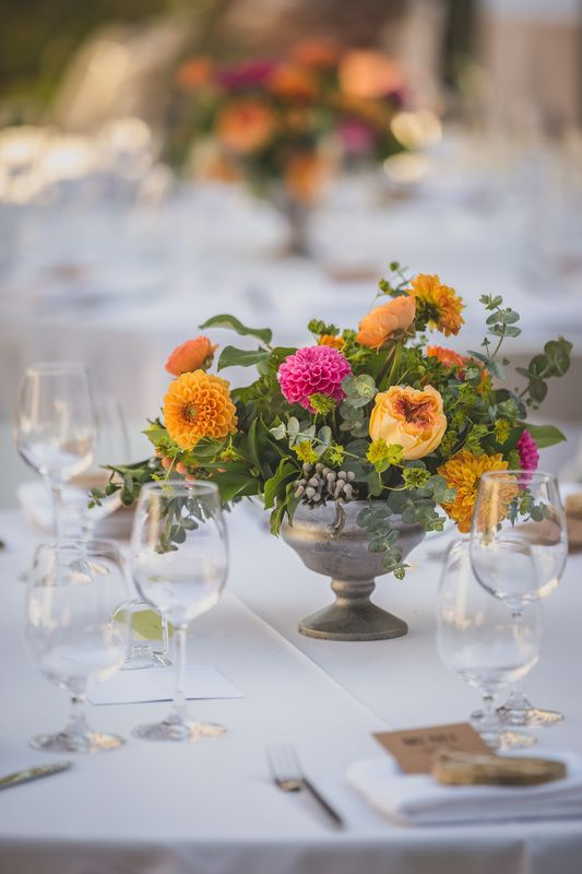 Peach and Coral Wedding at the Los Altos History Museum. This bright garden-inspired centerpiece features dahlias, garden roses and ranunculus with silver brunia berry in an antique silver compote.