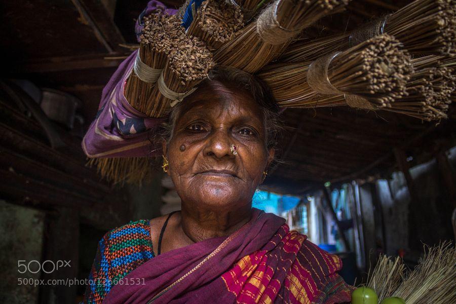Portrait of an old woman Portrait of an old woman carrying brooms on her head. Mumbai India.