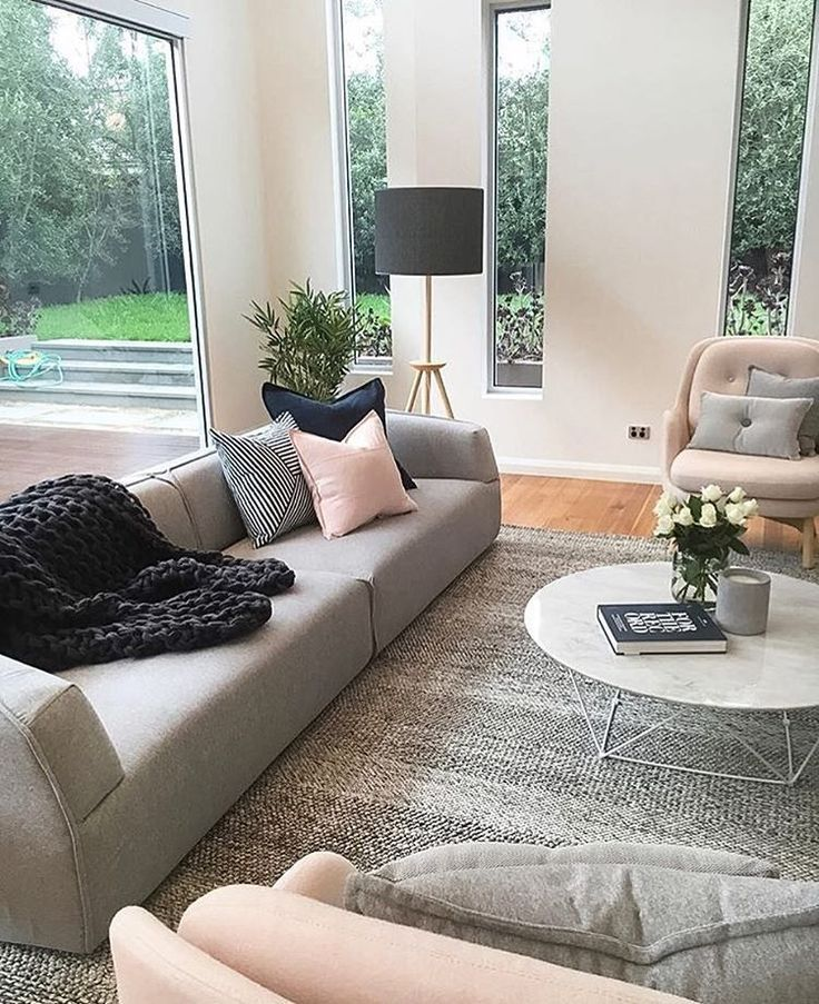 Wohnzimmer in grau-Rosa mit hellem Licht und tollen Kissen