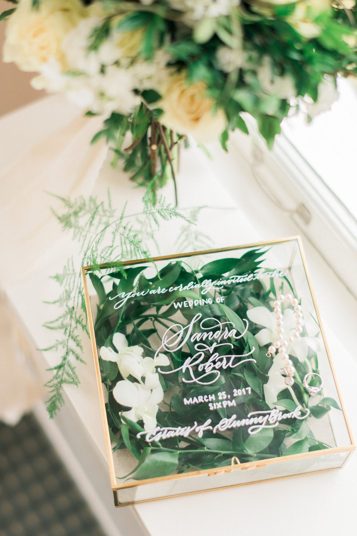 This non traditional wedding invitation handwritten on a gold brass glass box that not only serves as a wedding invitation but also a pre wedding keepsake