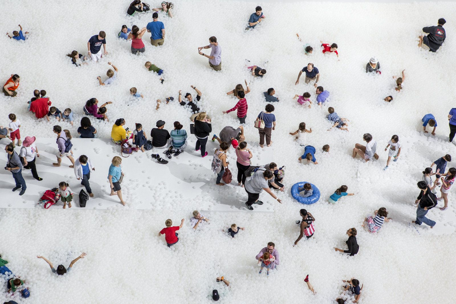"""Museumgoers play in the 10,000-square-foot exhibition called """"The Beach"""" at the National Building Museum in Washington, D.C."""