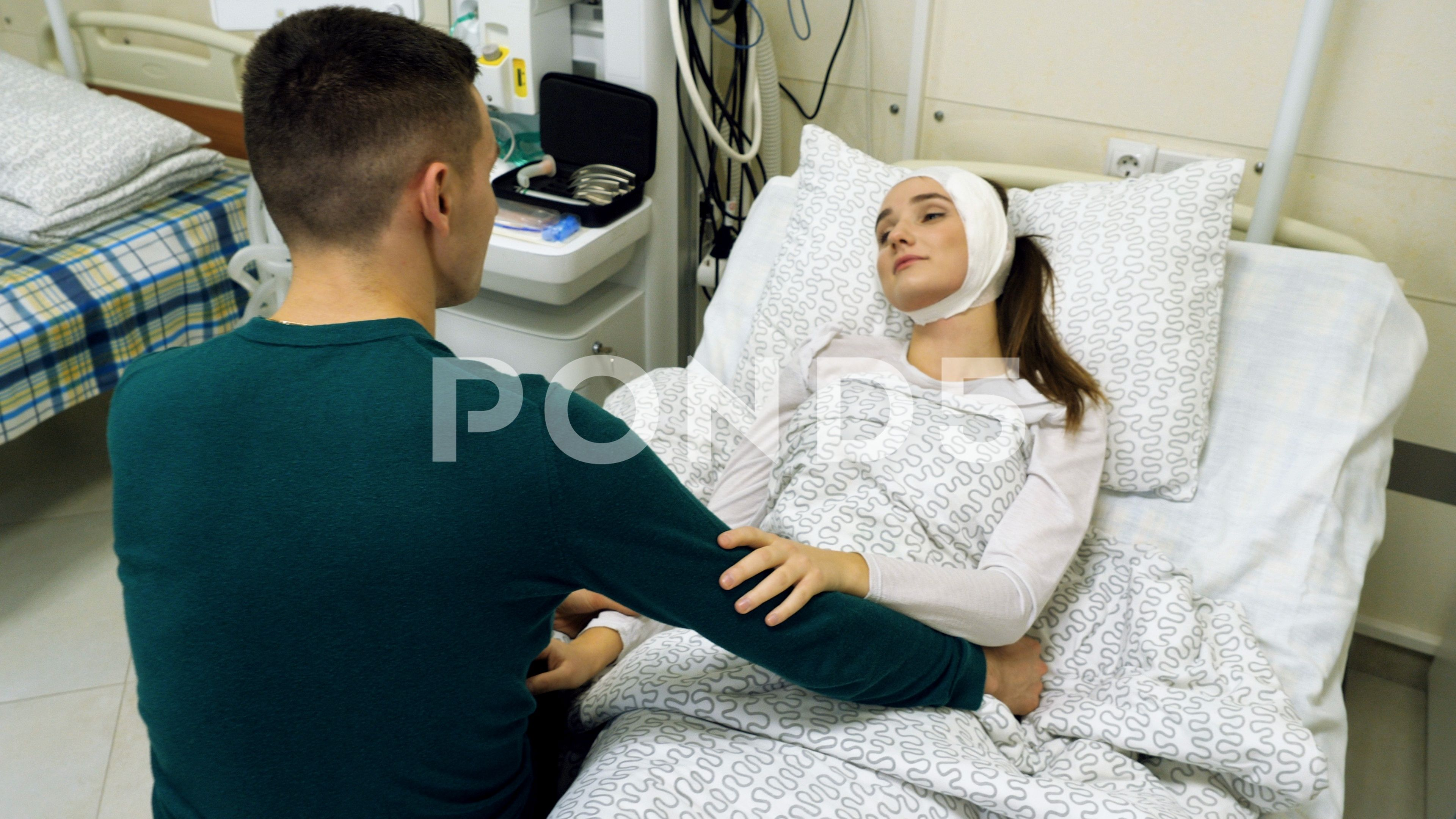 Woman lying on a hospital bed. Young man visiting his