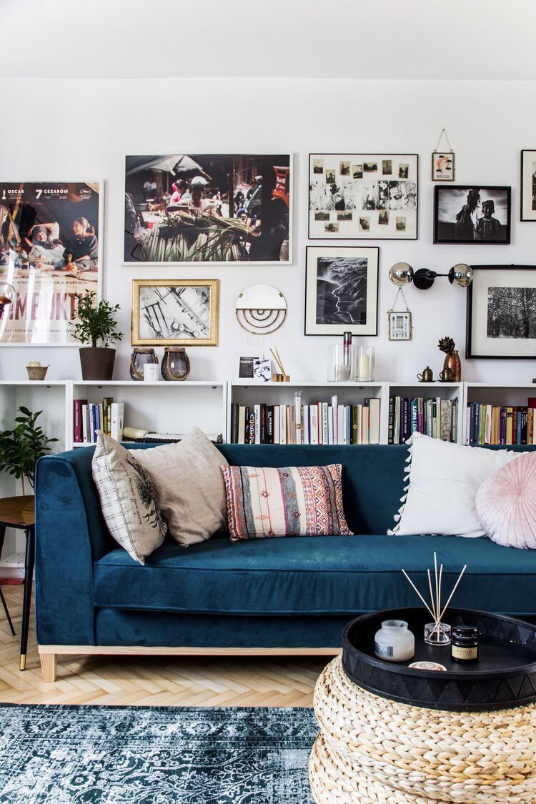 Boho Style Living Room With Blue Rug, Blue Couch, Book Shelf, And A Gallery  Wall.