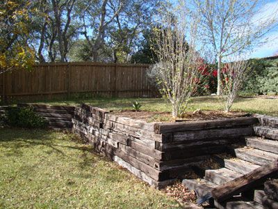 railroad ties, would be a great way to level things out and make the back yard more functional