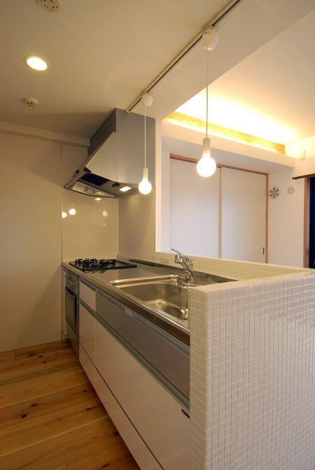 ペンダント照明とタイル腰壁のある開放的なキッチン 木のマンション