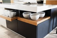 The Poggenpohl +MODO range with two glass drawers integrated beneath the long, L-shaped marble countertop, giving a lighter feeling to what ...