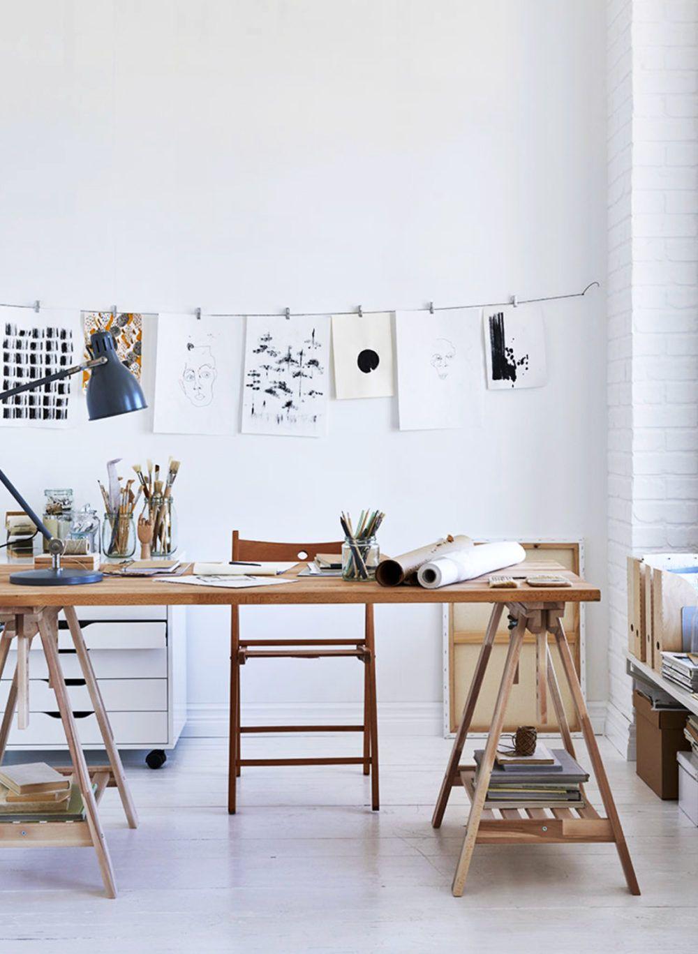 whitewashed art studio with sleek sawhorse table workspace. #workspace #artstudio #studio #whitewashed #paint #painting #sawhorsetable #sawhorsedesk #sawhorselegs #tasklamp #walldecor