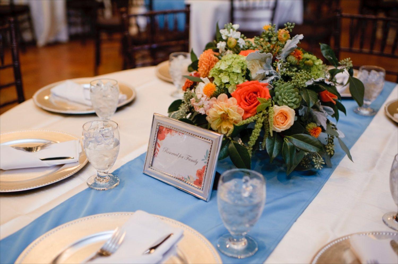 orange & teal wedding centerpieces | succulents roses hydrangeas amaranths dahlias dusty miller | Florist: The Moss & Rose