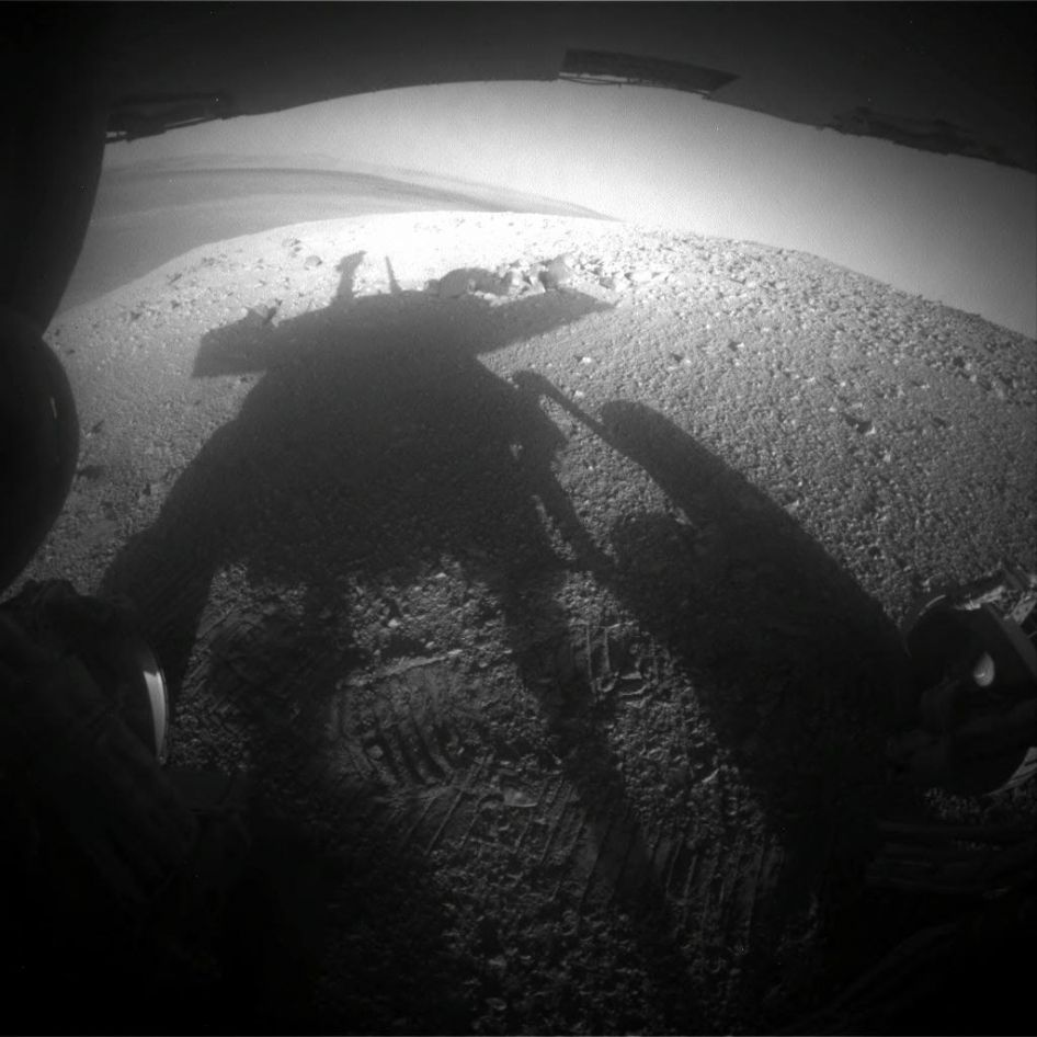 Shadow Portrait of NASA Rover Opportunity on Martian Slope - The image was taken looking eastward shortly before sunset on the 3,609th Martian day, or sol, of Opportunity's work on Mars (March 20, 2014). The scene includes a glimpse into the distance across the 14-mile-wide (22-kilometer-wide) crater. - Image Credit: NASA/JPL-Caltech