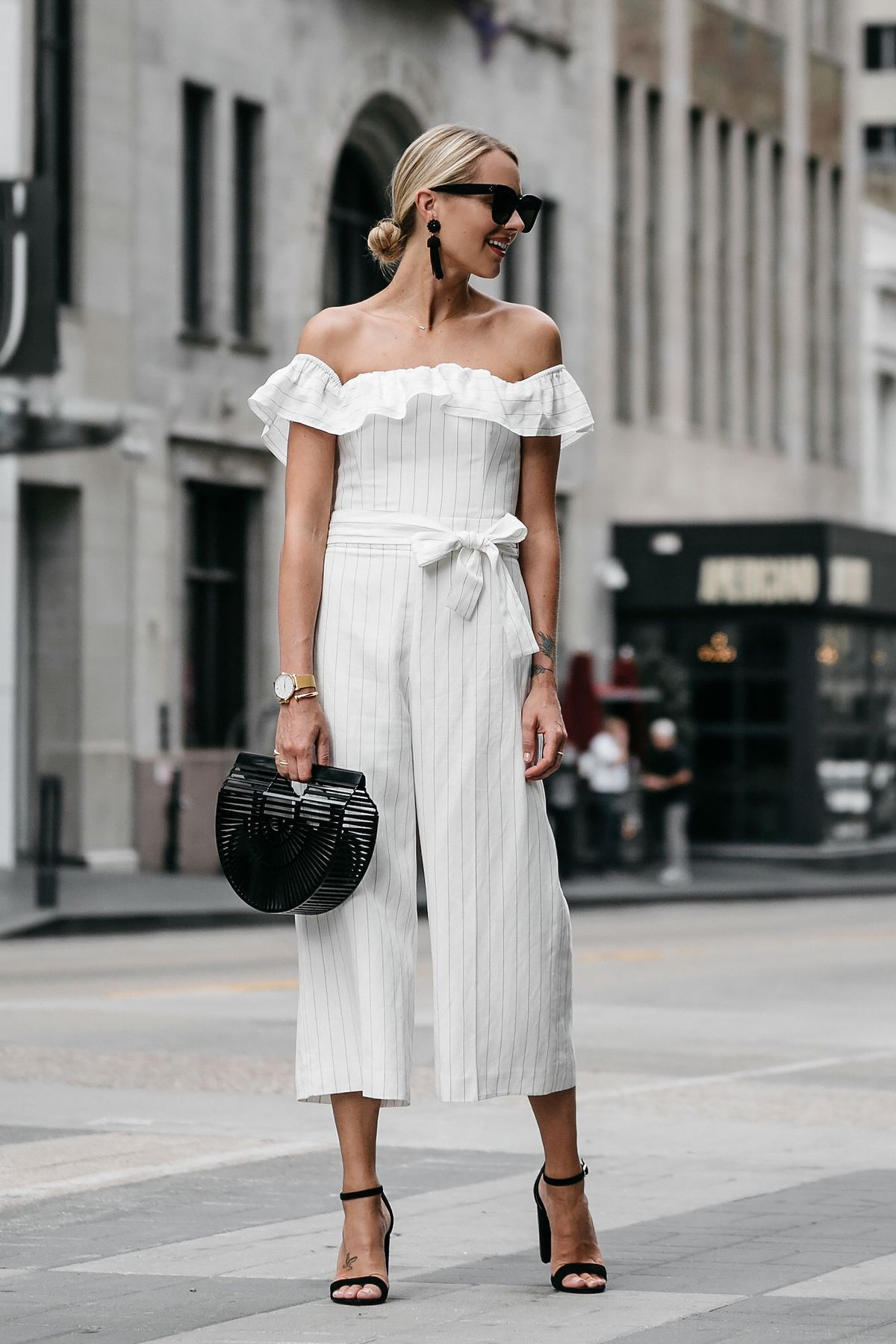 9f842b94d5c Blonde woman wearing Club Monaco off-the-shoulder ruffle white jumpsuit  Cult Gaia Black Acrylic Ark Clutch Black Ankle Strap Heeled Sandals Black  Tassel ...