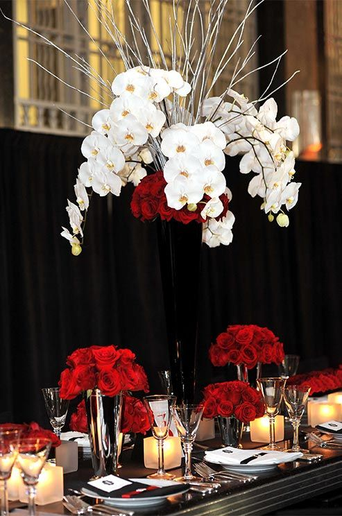 Crisp White Orchids And Frosted Branches Paired With Classic Red Roses Add Drama To A Black Tall Wedding CenterpiecesWhite