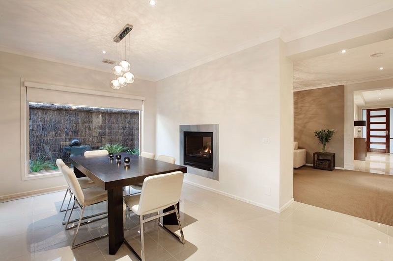 A living and dining area sharing a double sided fireplace