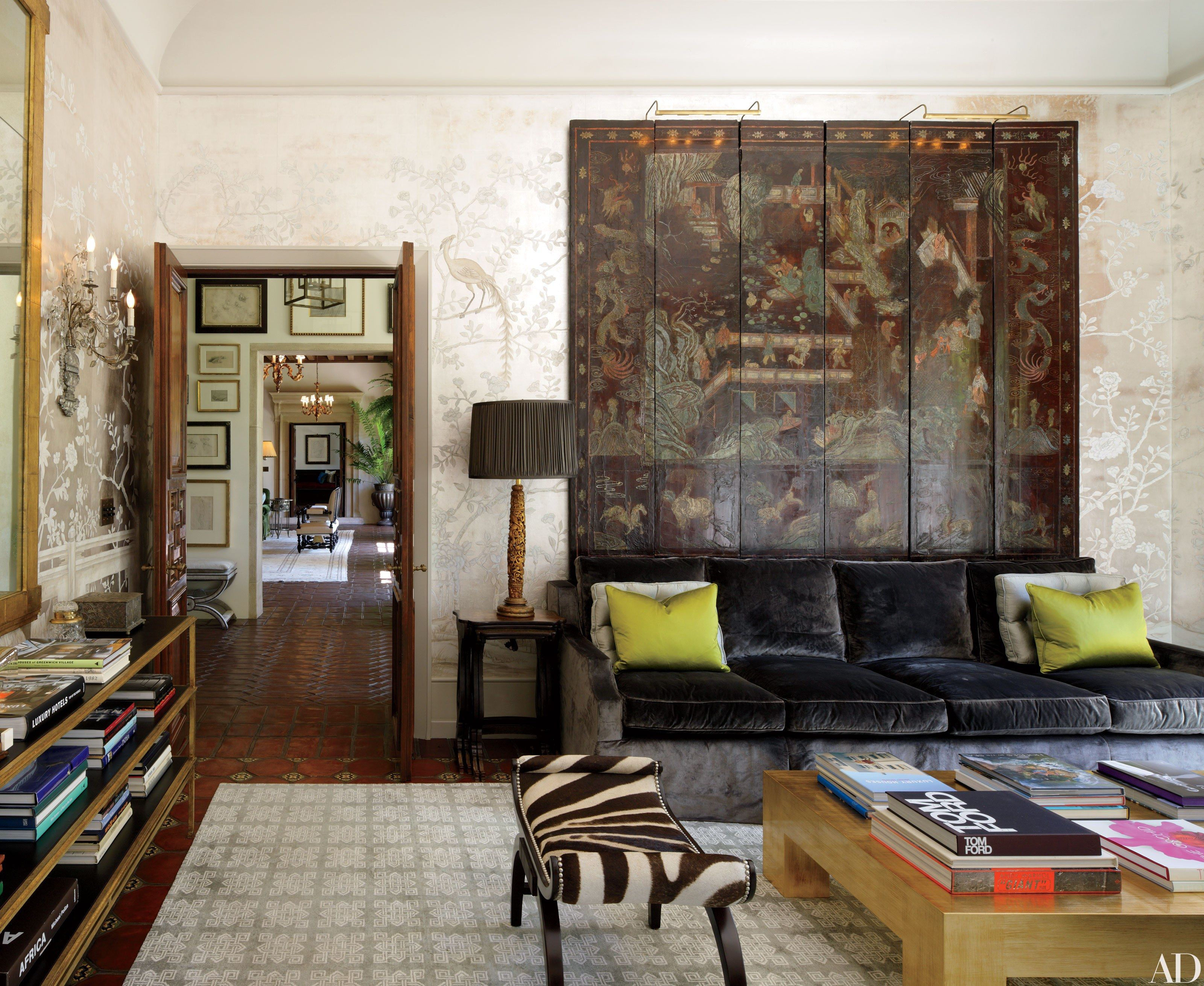 In the garden room of a Los Angeles home renovated by architect Marc Appleton and designer Windsor Smith, a 19th-century Chinese lacquer screen is displayed against silvered wallpaper with hand-painted additions in gouache by Scott Waterman. Furnishings include a Moderne gilded console table with leather shelves by Richard Shapiro Studiolo, a zebra-print stool from Paul Marra Design, and a Parsons-style low table from Eccola.