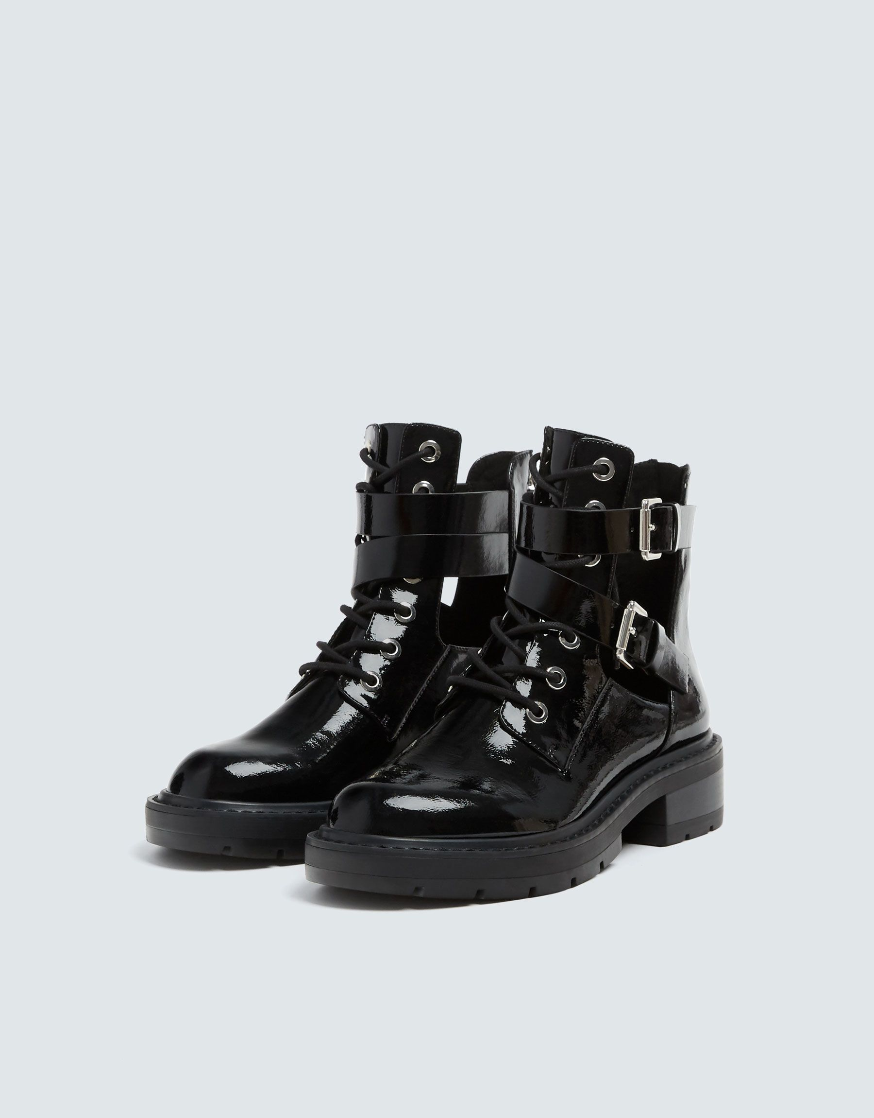 989599bcdb3 Black glossy finish lace-up biker ankle boots with die-cut details, zip on  the inside, buckles on the side and track soles. Heel height: 4 cm.