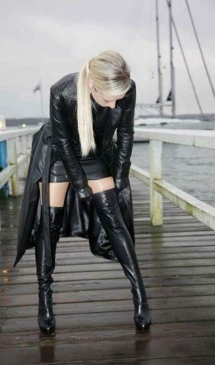 Blonde in black leather fetish outfit. Thigh boots gloves miniskirt trench  coat