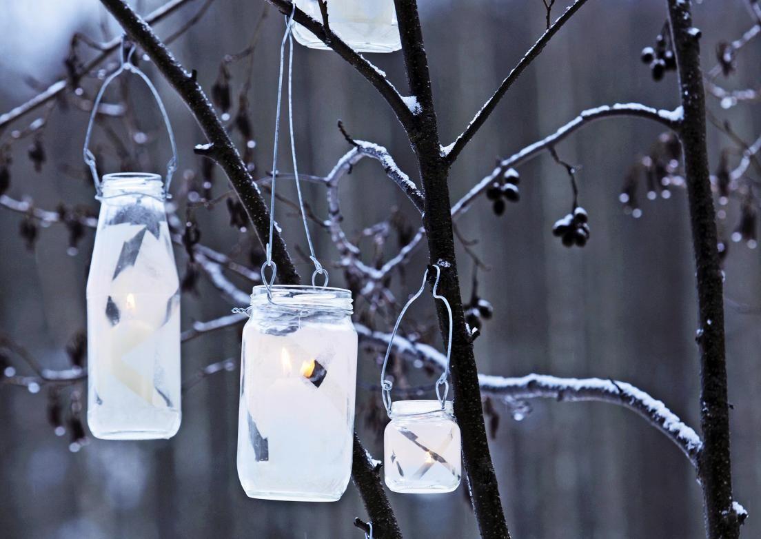 Koristele pihan puut itse tehdyillä lasilyhdyillä. Kun kaadat lasipurkin pohjalle karkeaa suolaa, se kerää valuvan steariinin paakuksi. Katso Meidän Mökin ohjeet!
