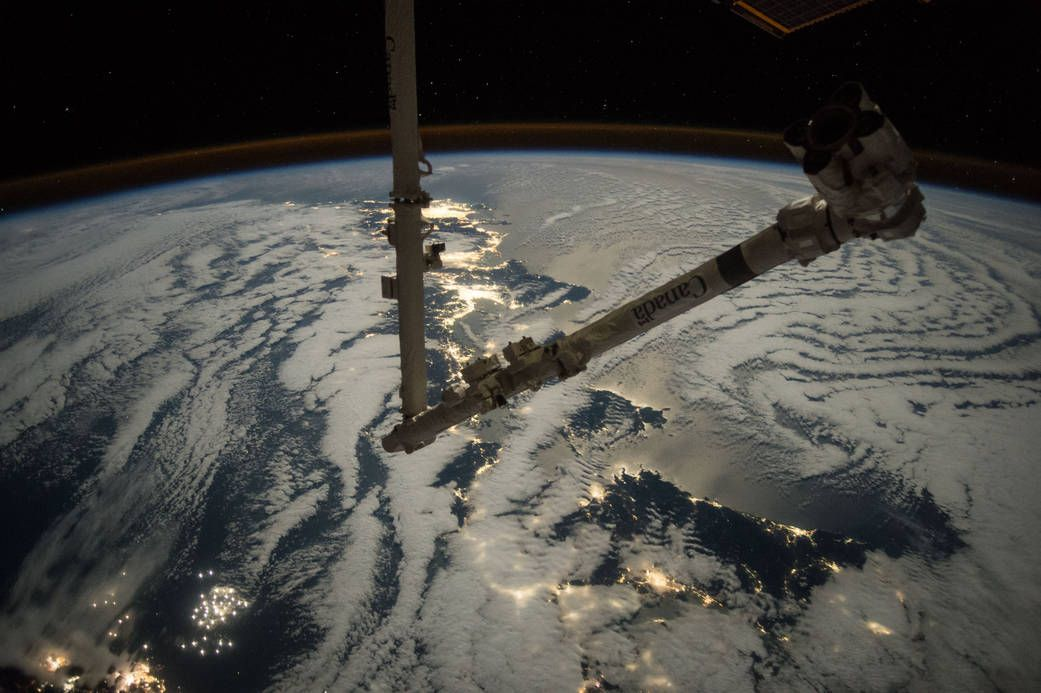 Canadarm2 with lights of Earth at night in background