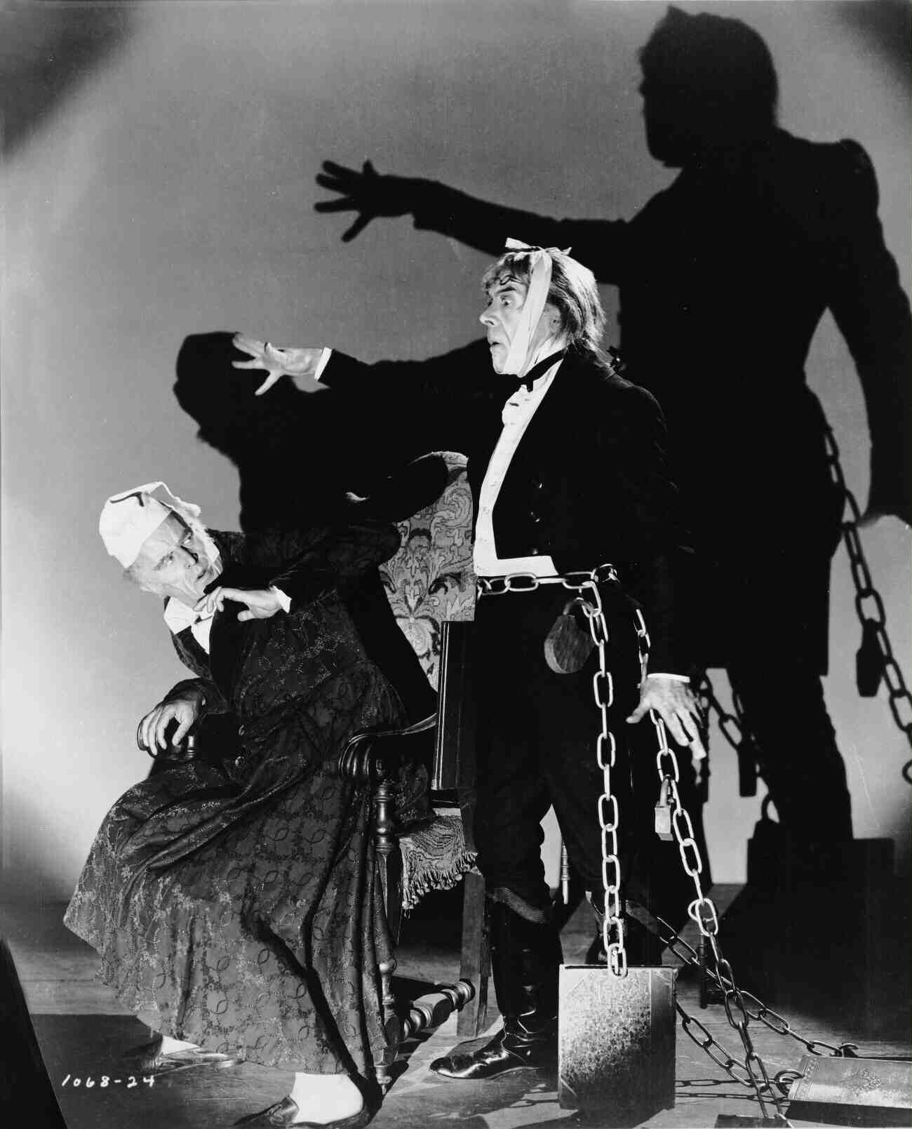 Full publicity shot of Reginald Owen as Ebenezer Scrooge, seated ...