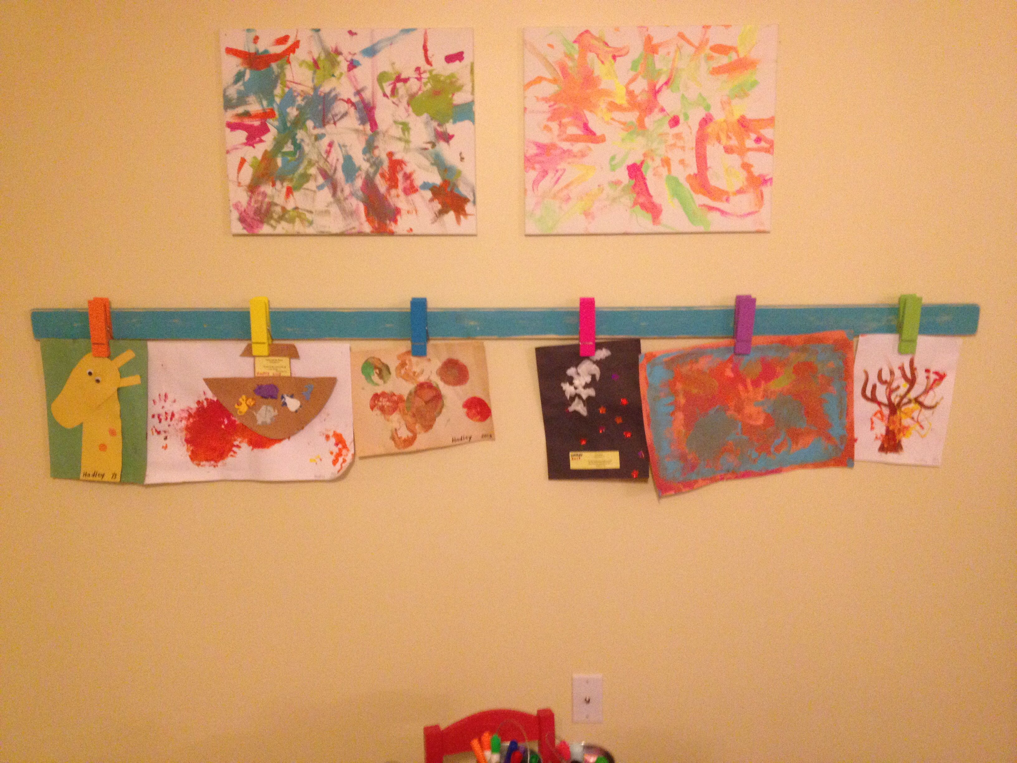Hang kids art.   Giant clothespins from michaels $1 isle mounted using wood glue.   Made by Andrew