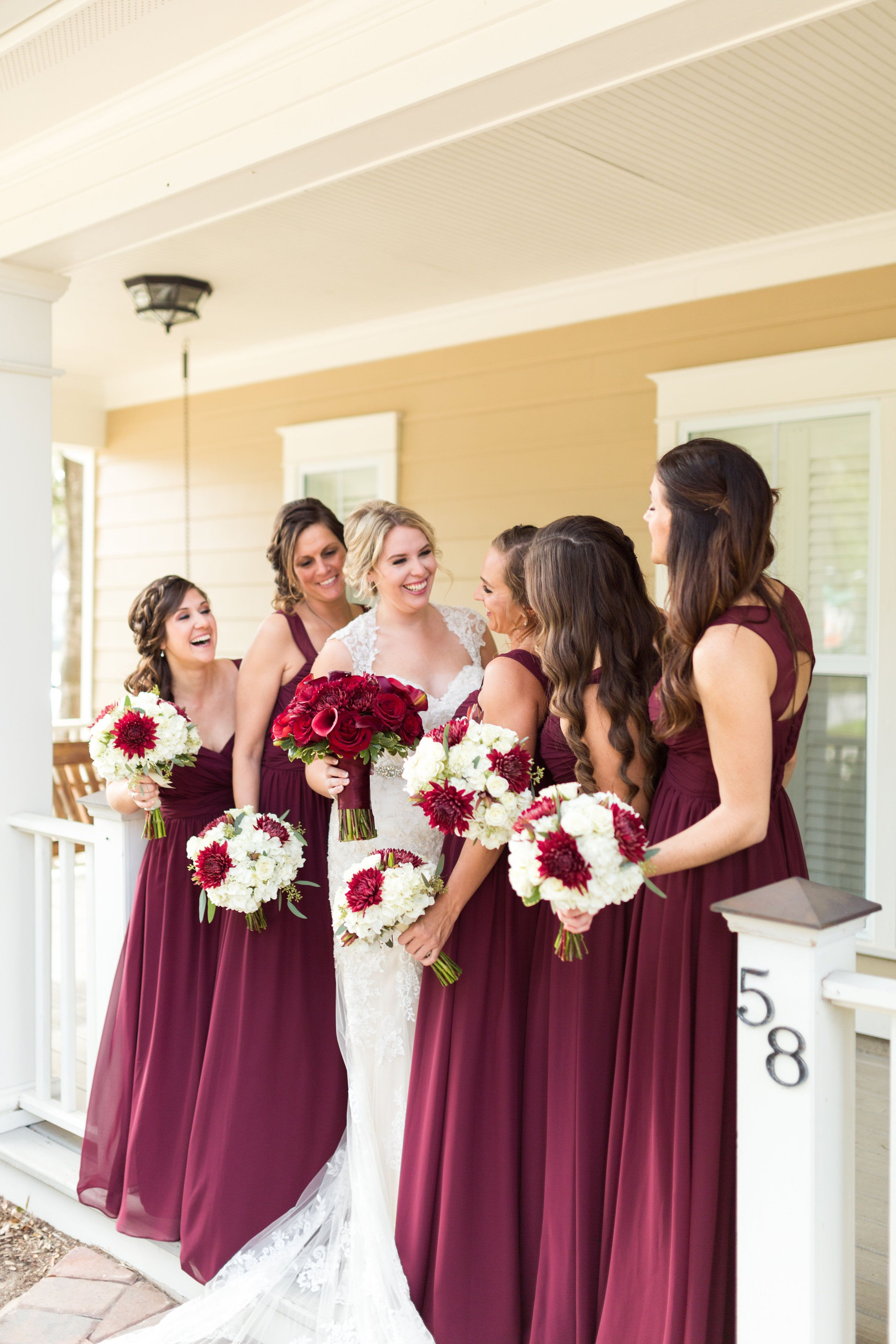 170d643ffb0 Bride and bridesmaids holding round bouquets in shades of red and white.  Christmas theme wedding. Maroon bridesmaids dresses.