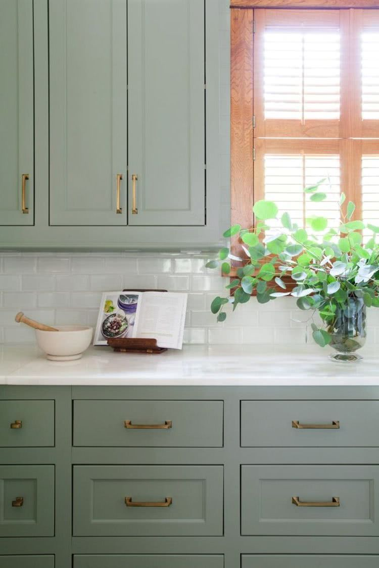 Single wall kitchen with sage green cabinets white marble