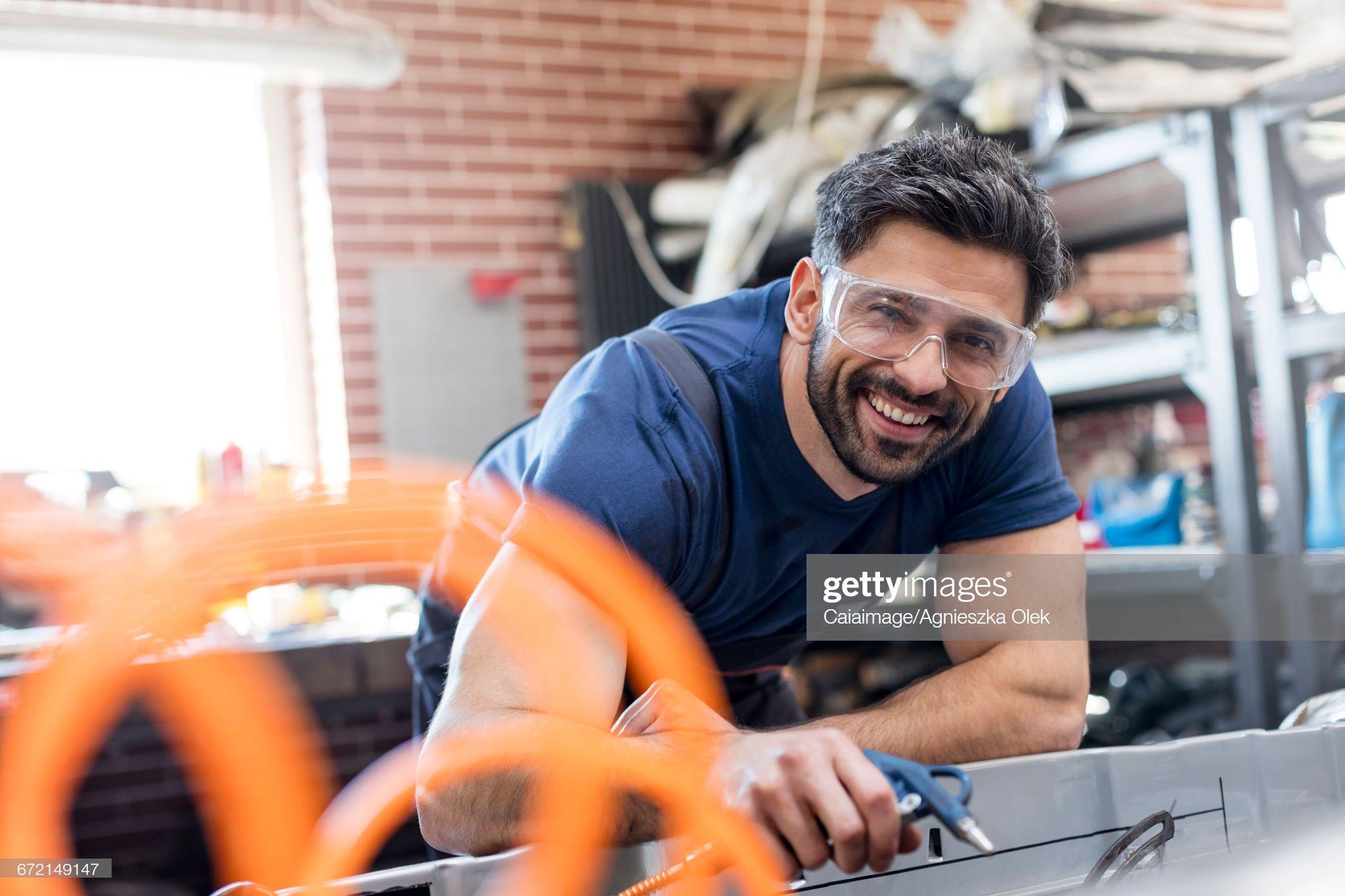 Stock Photo Portrait smiling mechanic working in auto