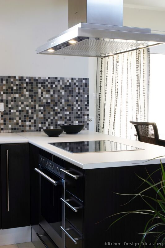 A Modern Black Kitchen With White Countertops A Sleek Stainless