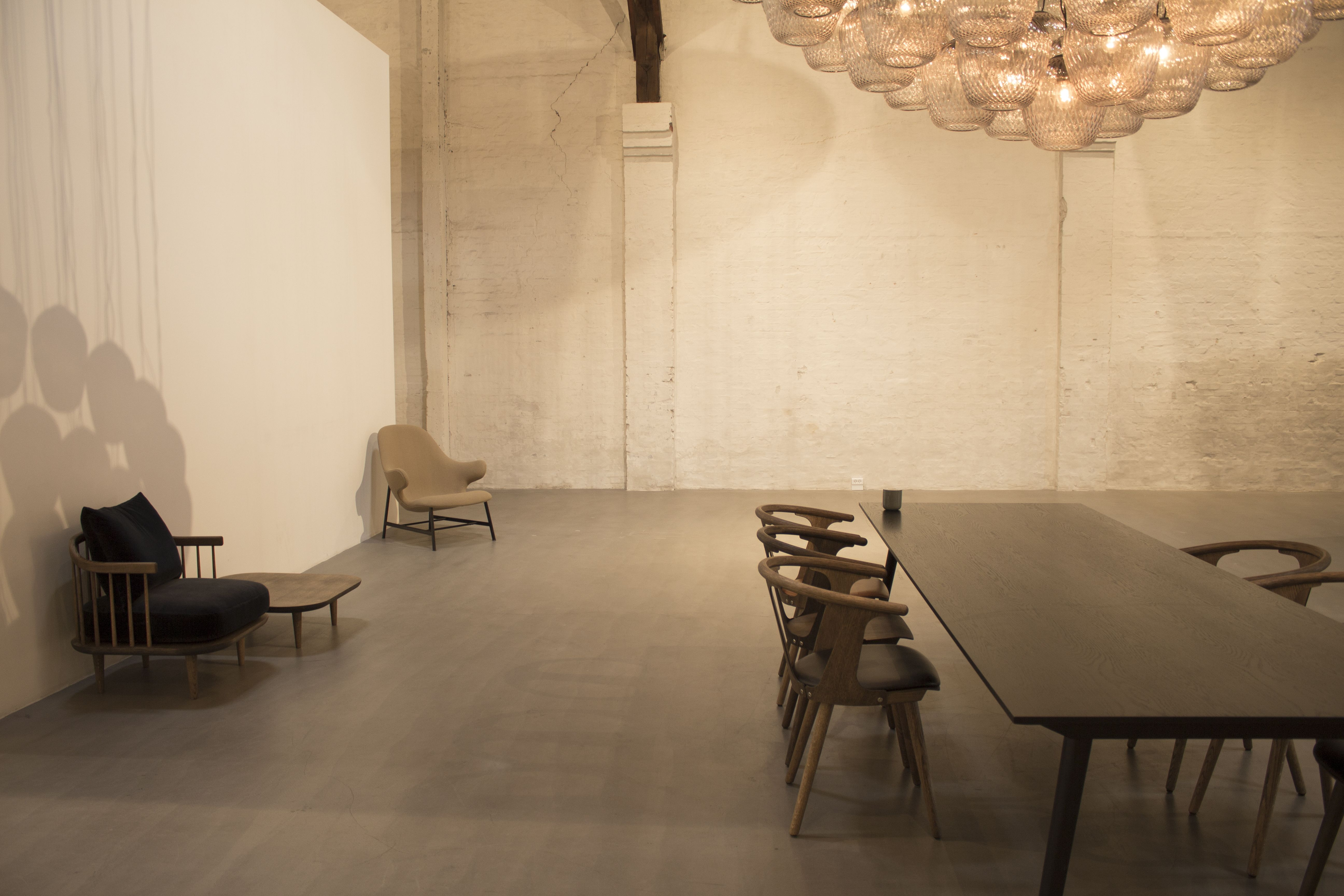 In Between Chairs And A Signature Blown Pendant Chandelier Sit At