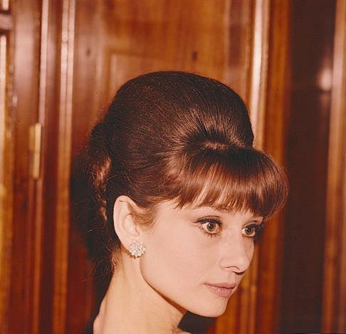 The actress Audrey Hepburn photographed by Angelo Frontoni during a cocktail at the Palazzo del Quirinale, located atPiazza del Quirinale, in Rome (Italy), held for the movie personalities who were awarded with the David of Donatello (the David di Donatello Award is the Italian equivalent of an Oscar), on March 13, 1964.Audrey was wearing:Earrings: Cartier (of diamonds, purchased by Audrey in 1959).