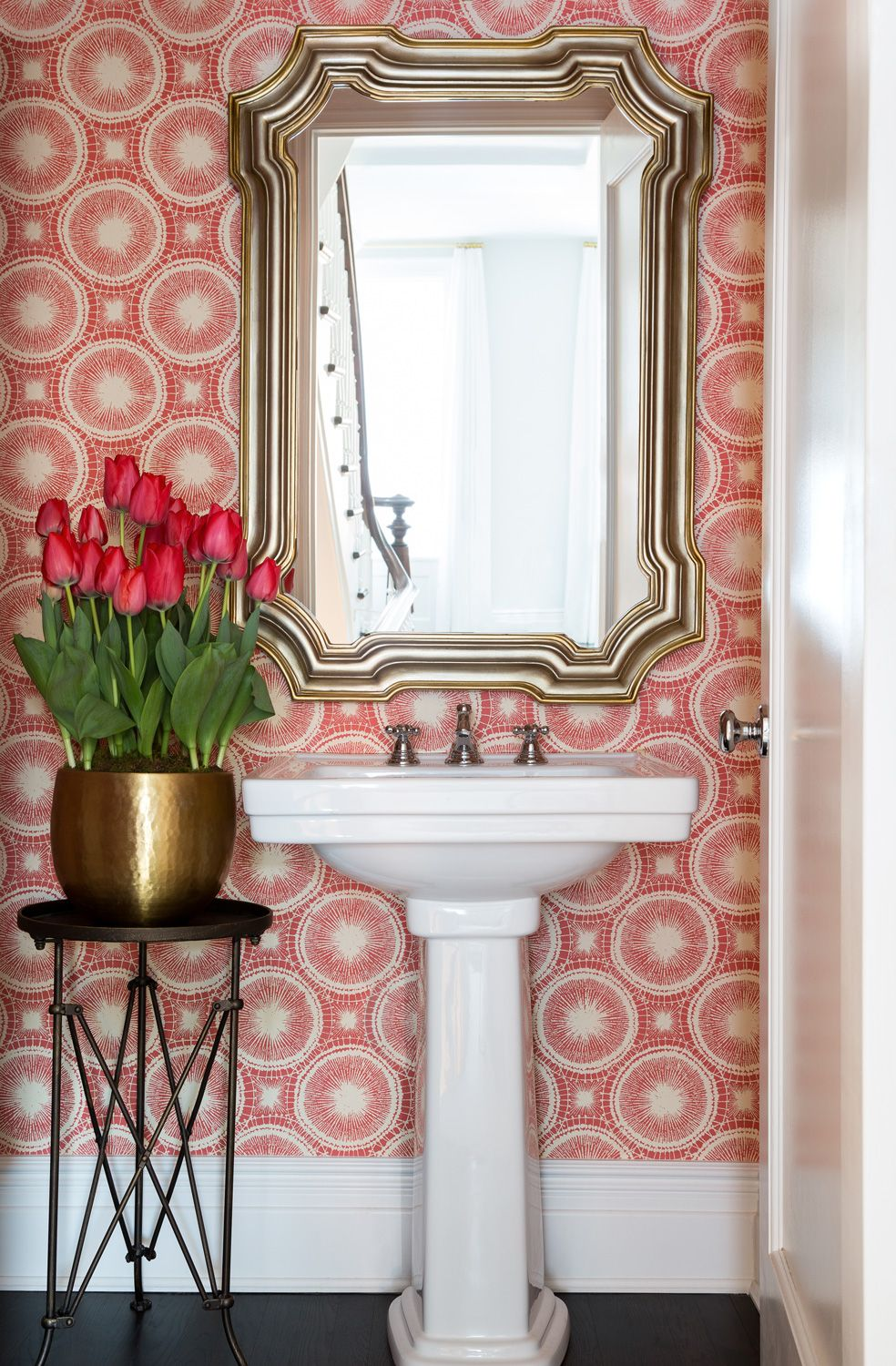Graphic wall paper and a bold mirror create a luxurious powder room. Photo by Ball & Albanese