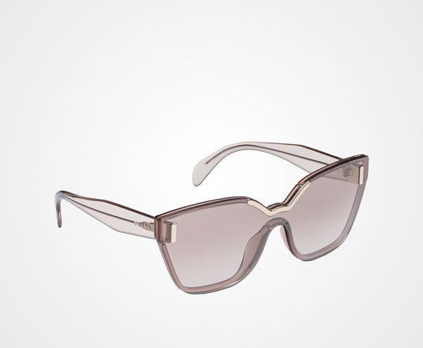 ab7edf61b41dc Prada Hide. Cat-eyed mono lens wraparound sunglasses characterized by the  transparent acetate frame front and sophisticated metal inserts.