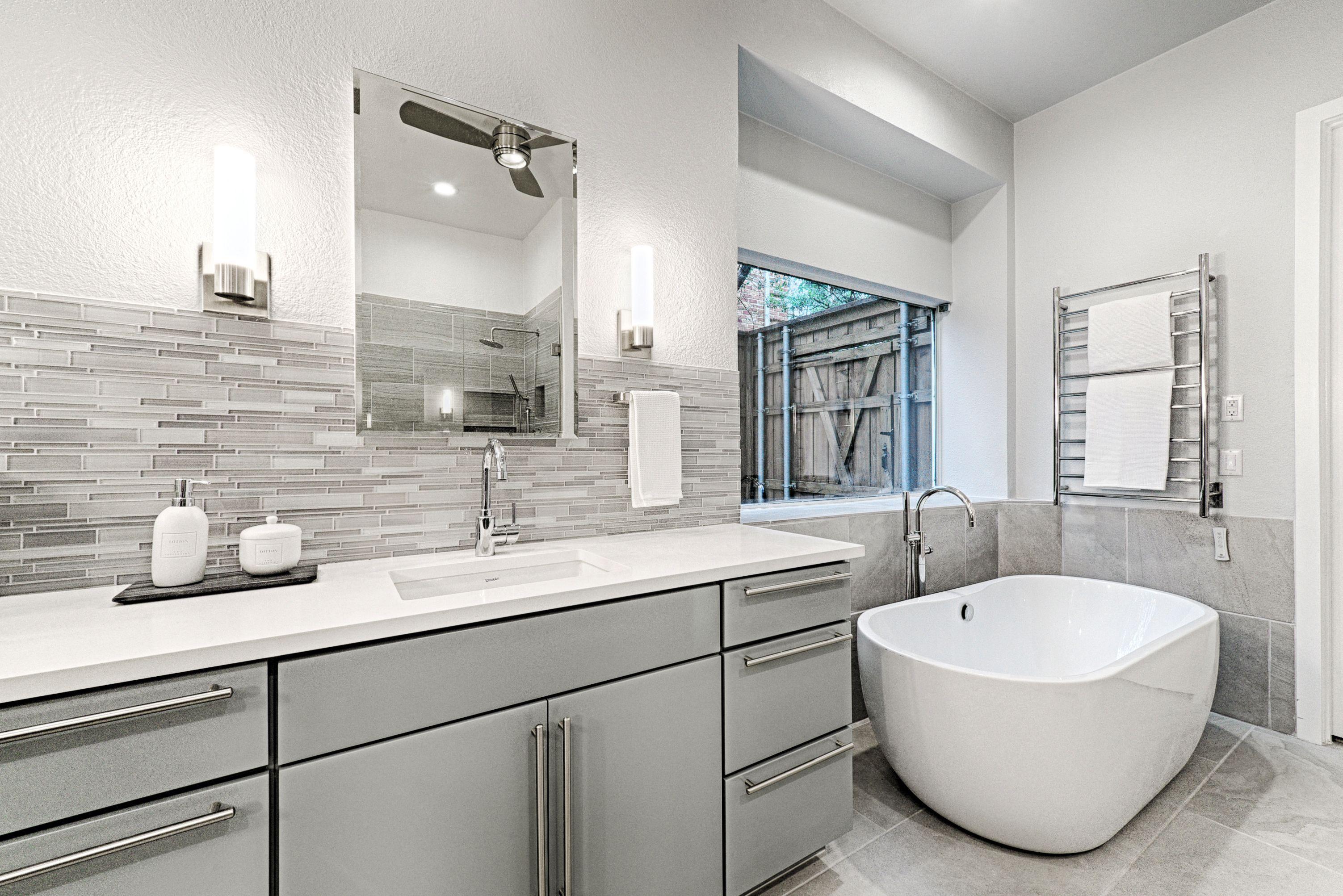 gorgeous bath remodel with freestanding tub and glass backsplash
