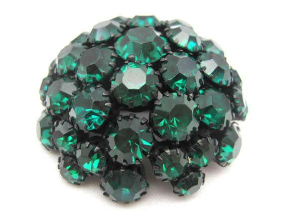 A stunning vintage brooch by Warner, featuring deep emerald green rhinestones set in black japanned metal. Measures about 2 across and about 1
