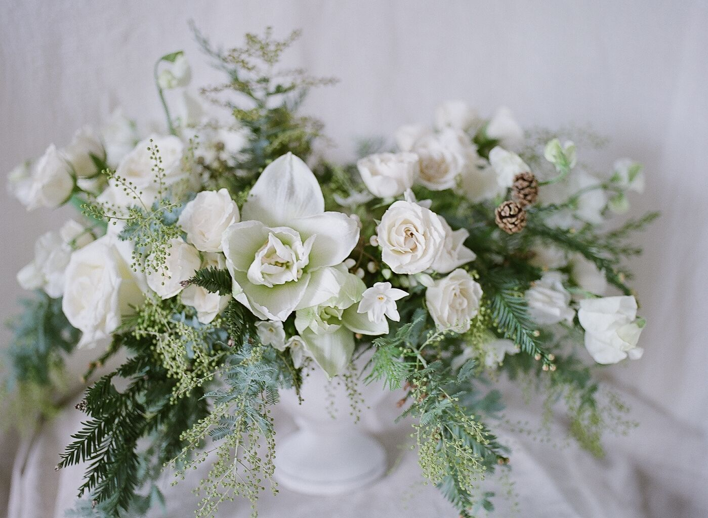 Winter White Centerpiece Featuring Acacia Amaryllis Majolica Roses
