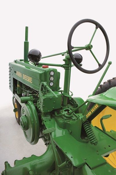 "John Deere two cylinder model HNH, equipped with PTO, hydraulic lift (the ""shin buster"" lever on the left side parallel to the floorboard) and electric start and lighting. All model H tractors were equipped with a 99.7cid (3.5625"" bore x 5.0000"" stroke), 4.75:1 compression ratio, all fuel engine that developed 12.48 hp at the drawbar and 14.84 hp on the belt, at 1,400 RPMs."