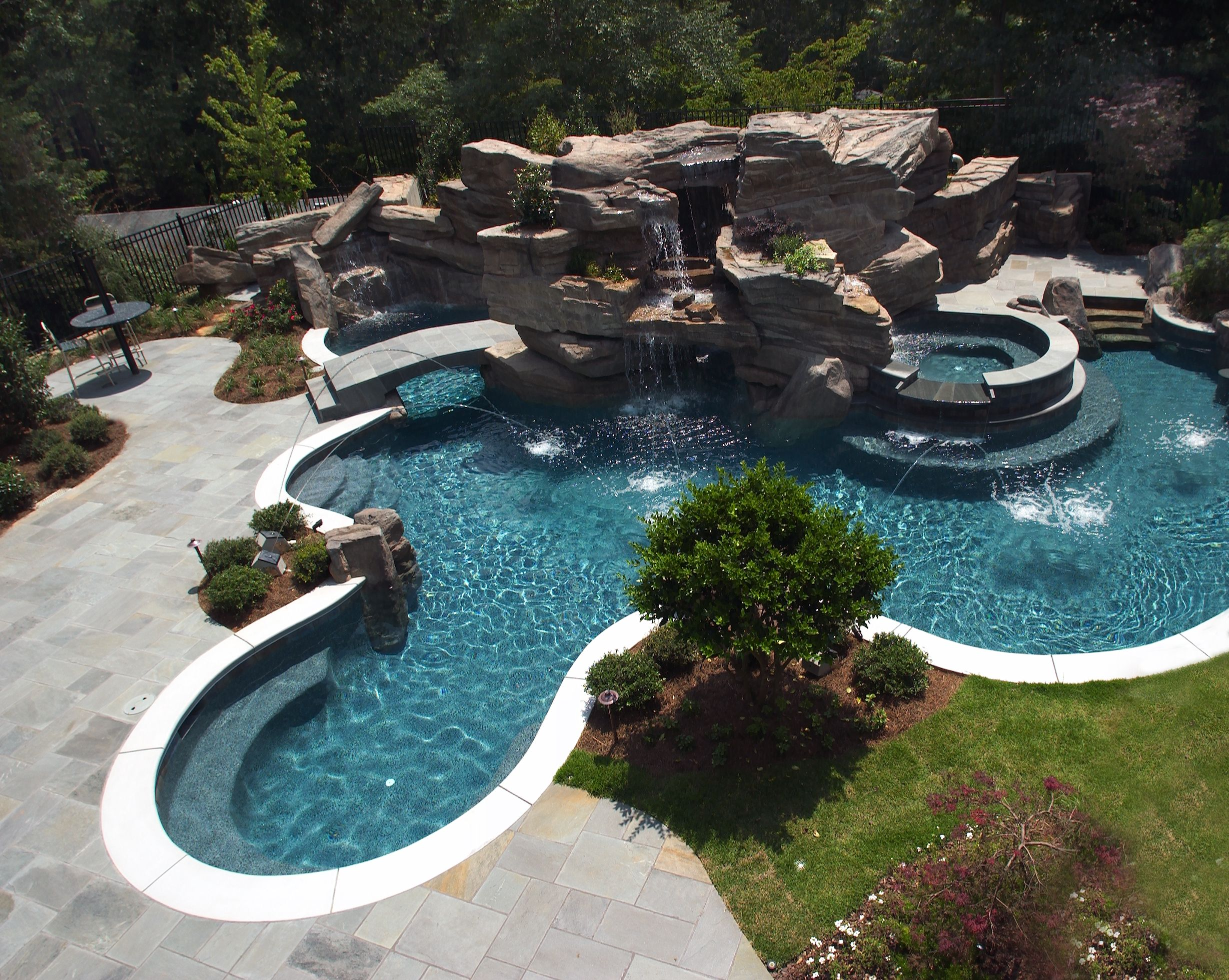 Elaborate swimming pool featuring large grotto waterfall for Pool design with slide